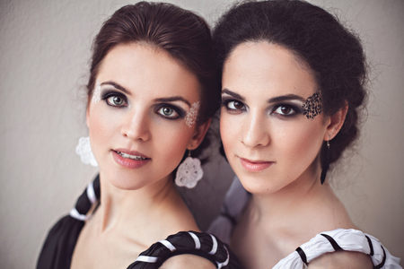 fantasy makeup: Vogue style photo of two ladies in black and white long dresses with fantasy make-up