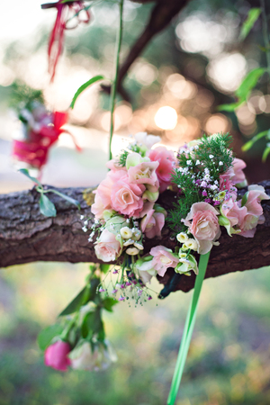 spring green: Wedding decoration of glas bottles with flowers hanging on the tree Stock Photo