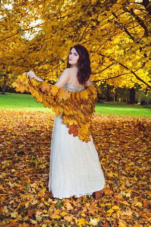 Woman wearing a white dress, autumn leaf shawl while posing for a photograph under the autumn tree in the forest