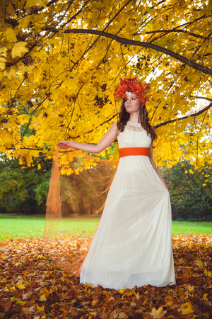 Woman wearing a white dress and leaf wreath while posing for a photograph under the autumn tree in the forest