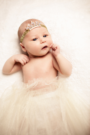bed skirt: Portrait of a cute baby girl wearing princess crown headband and ballet skirt while lying down on a bed