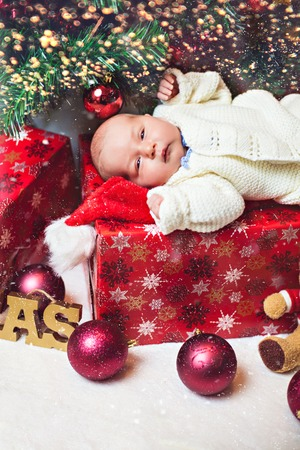Portrait of newborn baby boy white clothes lying under christmas tree with many gifts