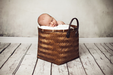 innocense: Cute baby girl asleep in basket with soft lining Stock Photo