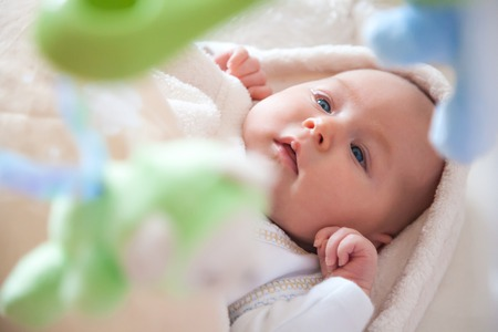 attention grabbing: Cute newborn baby girl with toys hanging above her head, grabbing her attention