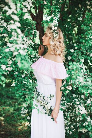 Young woman in white-pink dress standing white colored blooming trees Stock Photo