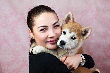 Woman Keeping Akita Puppy Near Her Face