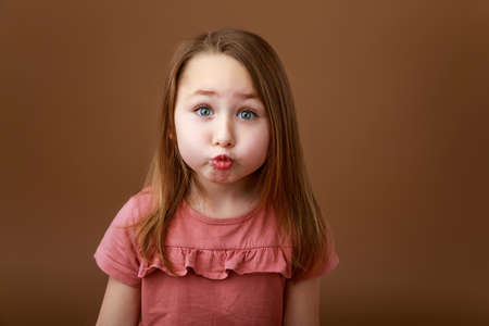 Little funny girl stretching her lips in a kiss Reklamní fotografie