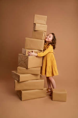 Little curly girl with a big stack of gifts for the holiday