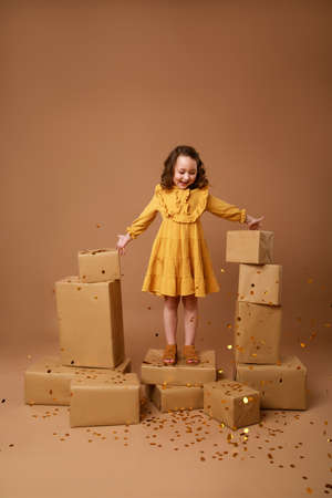 Little curly girl with a stack of gifts for the holiday and gold confetti