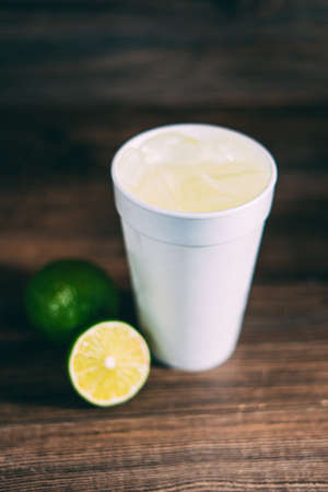 A disposable  cup and a citrus fruit