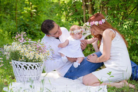 lifestile: Family portrait outdoors picnic. Baby girl and her parents. Sunny Summer day Family Picnic. Happy family concept. Beautiful kid playing outside with parents.Young family spending time on a summer day Stock Photo