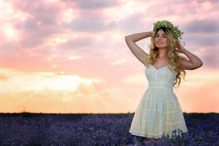 Beautiful Girl in lavender Field at sunset. Pretty woman Provence style in a dress and flowers wreath. Beautiful blonde woman in the lavender field on sunset Amazing portrait