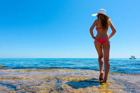 Young woman on the coast of the island. Portrait of a girl in white hat looking at a boat sailing in the sea. Beautiful Summer sea side with turquoise water. Cyprus island, Protaras. View from behind