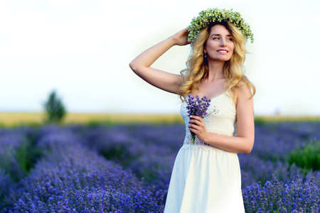 Beautiful Girl in lavender Field. Pretty woman Provence style in white dress and flowers wreath. Beautiful blonde woman in the lavender field on sunset Amazing portrait