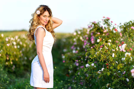 Girl in the poppy field . Happy young woman smiling in the meadow of nature. Beautiful sunset light. Vintage Provence style portrait Stock Photo