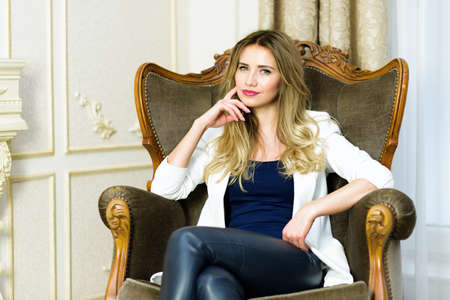 curled lip: Blonde Girl in leather pants sitting in a couch. Luxury interior scene. Studio shot