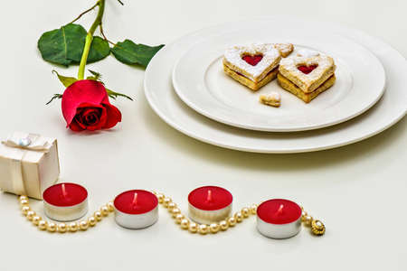 passion fruit flower: Homemade Heart shaped Almond Linzer cookies on white plate. Romantic set up red roses and candle lights ffor anniversary, wedding, Valentine Day Stock Photo