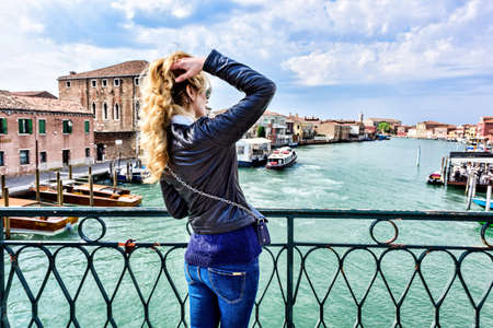 Woman walking in Murano island Italy. Traveler or tourist girl exploring the city