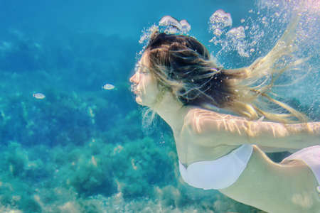 Girl and small fishes swimming underwater portrait. Sea summer blue water background with bubbles