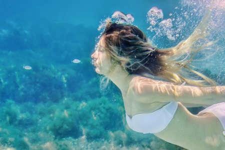 Portrait sous-marin de fille et de petits poissons. Fond de l'eau bleue de la mer avec des bulles Banque d'images