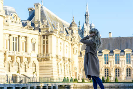 Woman at Chantilly Palace. Young tourist girl admiring the views. Portrait soft bokeh backgrounds