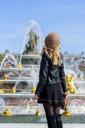 Woman at Versailles Palace. Young french dressed tourist girl admiring the view. Portrait from the back. Fountaine backgrounds