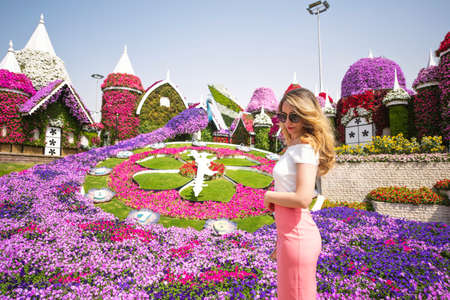 Woman in Dubai Garden portrait. Sunny day beautiful flowers backgrounds