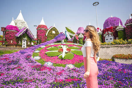 Woman in Dubai Garden portrait. Sunny day beautiful flowers backgrounds 版權商用圖片