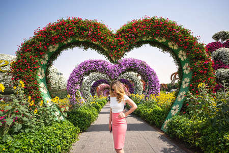 Woman in Dubai Garden portrait. Sunny day beautiful flowers backgrounds