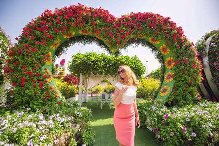 Donna nel ritratto del giardino di Dubai. Giornata di sole bellissimi sfondi di fiori