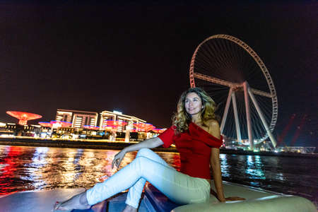 Woman in Dubai Marina, United Arab Emirates. Attractive girl admiring Marina view at nights Фото со стока
