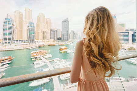 Woman in Dubai Marina, United Arab Emirates. Attractive lady wearing a long dress admiring Marina daylight views 免版税图像 - 122396388