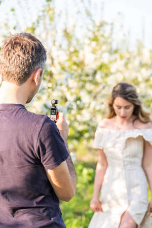 Man filming a model with a modern video camera in an orchard. Spring time shooting ideas. Behind the scenes shooting vlogs