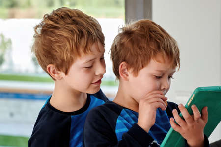Two little boys playing with tablet in green case. Happy brothers playing games with gadgets