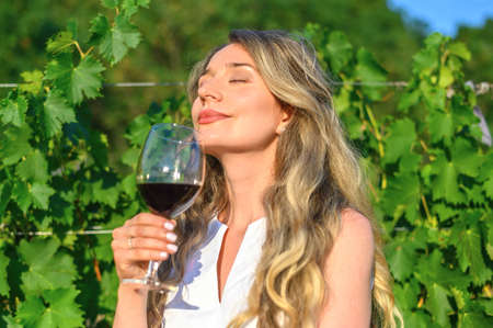 Woman smelling wine aroma taste. Happy girl drinking wine. Beauty lady with a glass of wine dreamy looks