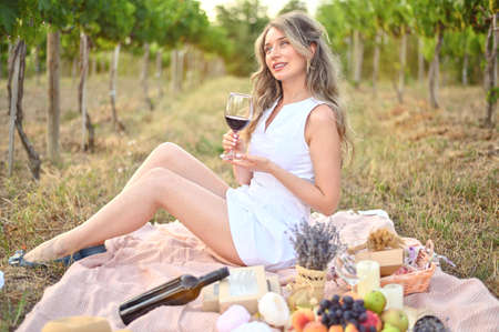 Woman having a picnic with a glass of wine. Vine yard green backgrounds