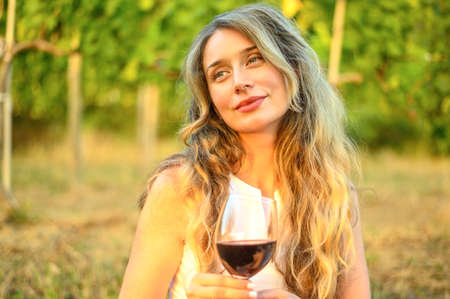 Woman at the picnic with a glass of wine. Vine yard green backgrounds