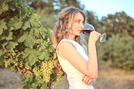 Woman with a glass of wine dreamy looks, Happy girl drinking wines