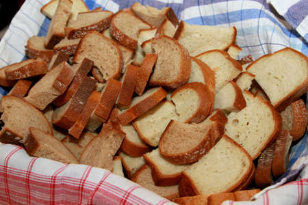 Bread slices in basket with blue kitchen cloth, close-up
