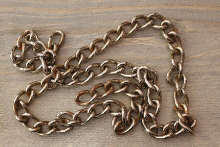 Chain of metal on wood background Reklamní fotografie