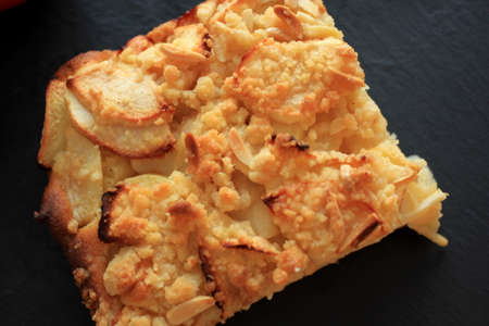 Fresh homemade apple pie with crispy crust close up, top view, black background