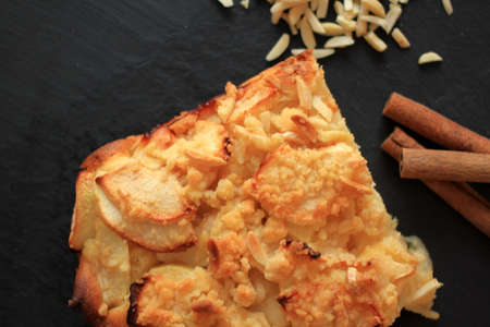 Fresh homemade apple pie with cinnamon sticks and almond slivers, top view, black background