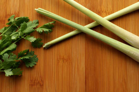 Lemongrass and few coriander leaves on bamboo board, top view, copy space