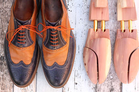 Brown and blue leather shoes and cedar shoe stretchers on wooden background