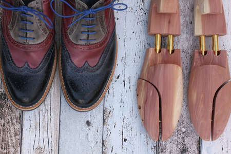 Red and blue leather shoes and cedar shoe stretchers on wooden background