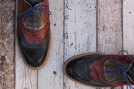 Red and blue leather shoes on wooden background