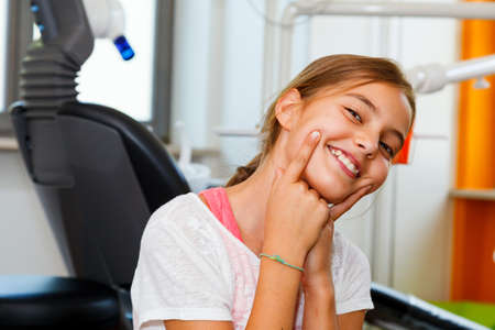 dent: Funny and happy little girl in a dental surgery with big smile