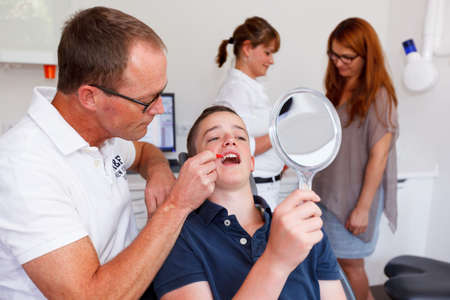 explains: A doctor explains a young boy how he can care the teeth