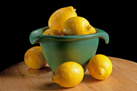 Green kitchen bowl with a group of lemons