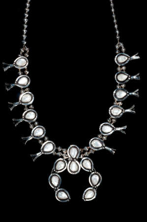 Silver squash blossom navajo necklace with opal gems on black background Imagens